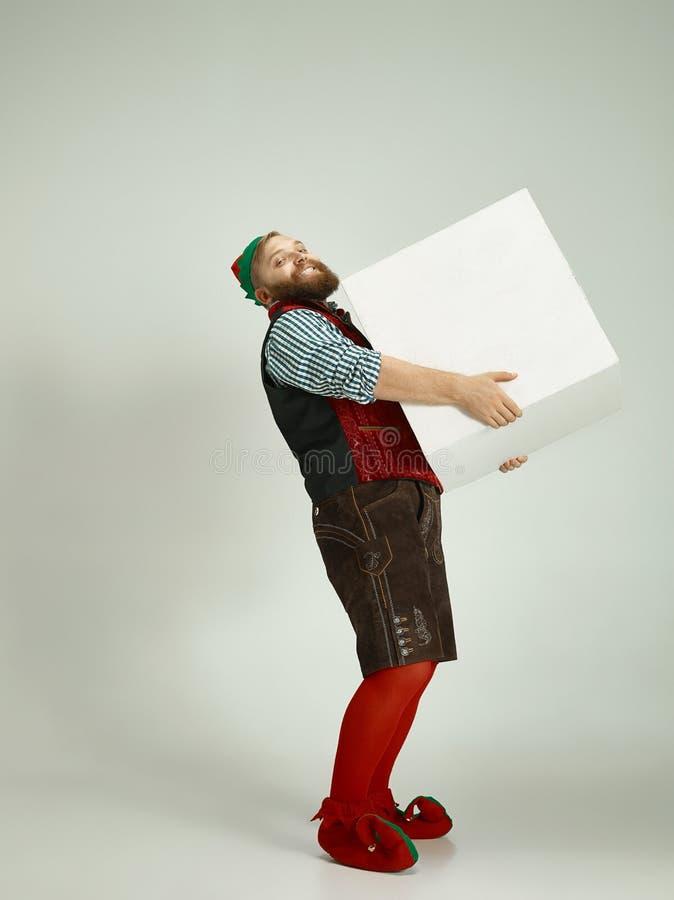 Hombre amistoso vestido como un gnomo divertido que presenta en un fondo gris aislado foto de archivo