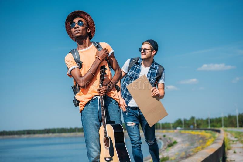 hombre amrican africano joven con la guitarra que hace autostop fotografía de archivo