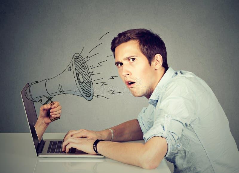 Hombre ansioso que se sienta en la tabla usando el trabajo en un ordenador con el megáfono que empuja hacia fuera de una pantalla fotografía de archivo libre de regalías