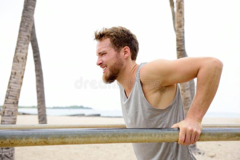 Hombre apto de la cruz que se resuelve haciendo ejercicios de las inmersiones imagen de archivo libre de regalías