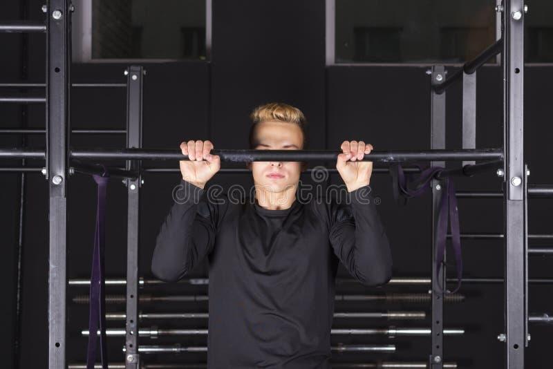 Hombre apto de los jóvenes fuertes que hace tirón-UPS en una barra en un gimnasio imágenes de archivo libres de regalías