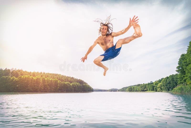Hombre apto de los jóvenes que hace un salto en un lago imagen de archivo libre de regalías