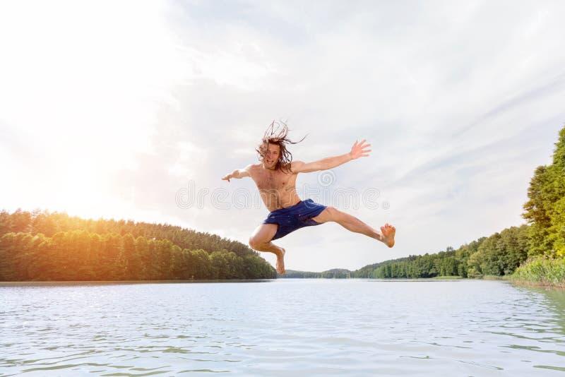 Hombre apto de los jóvenes que hace un salto en un lago fotografía de archivo libre de regalías