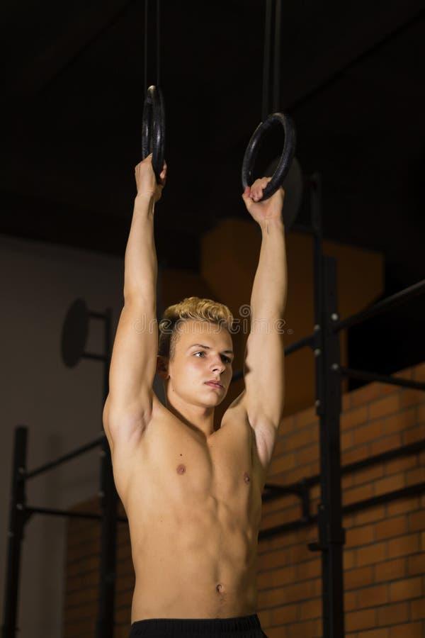 Hombre apto de los jóvenes que levanta en los anillos gimnásticos El culturista en el gimnasio está entrenando, el fondo oscuro M imagenes de archivo