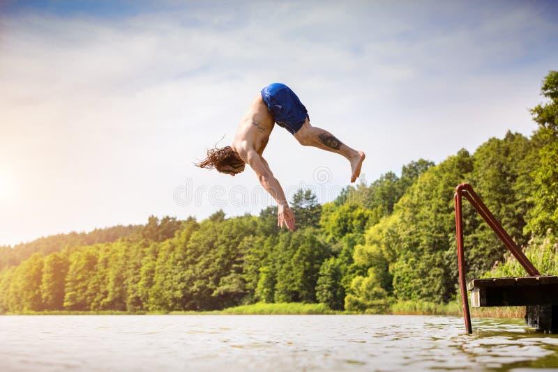 Hombre apto de los jóvenes que salta en un lago fotografía de archivo libre de regalías
