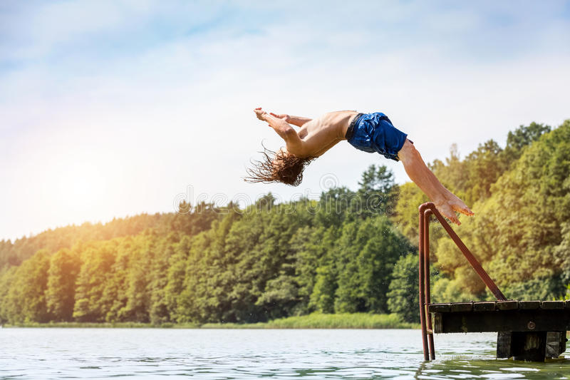 Hombre apto de los jóvenes que salta en un lago fotos de archivo