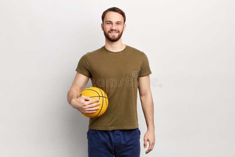 Hombre apto hermoso en la ropa casual que juega con una bola foto de archivo
