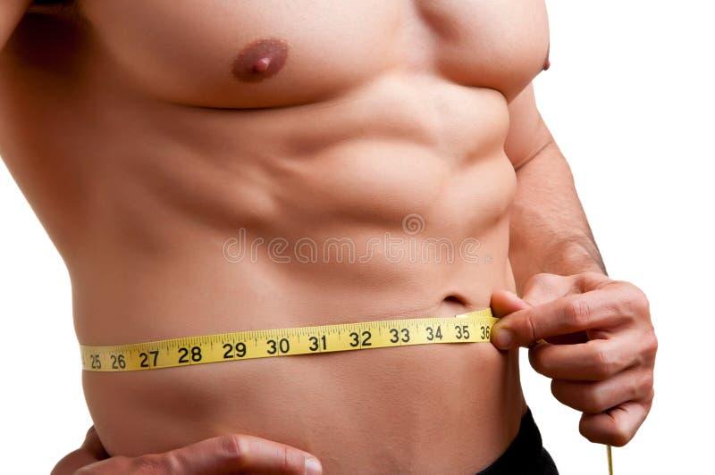 Hombre apto que mide su cintura fotografía de archivo