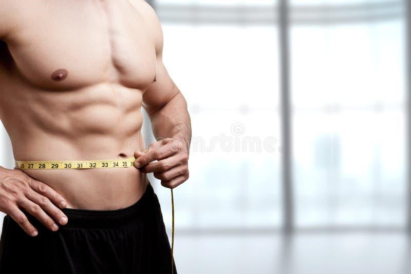 Hombre apto que mide su cintura fotografía de archivo libre de regalías