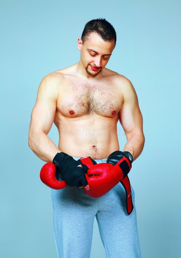 Hombre apto que pone sus guantes de boxeo fotos de archivo