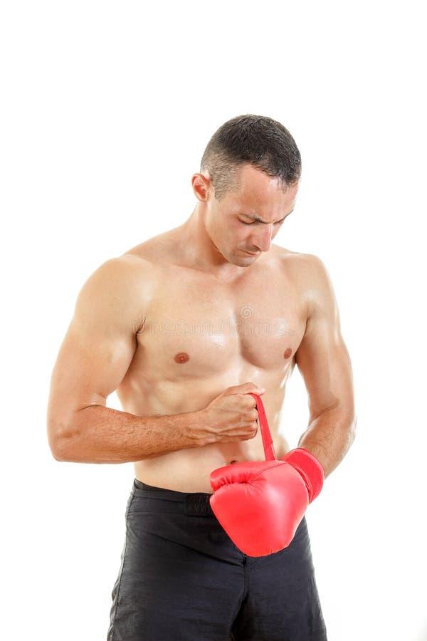 Hombre apto que pone sus guantes de boxeo, preparándose para entrenar sobre w fotografía de archivo