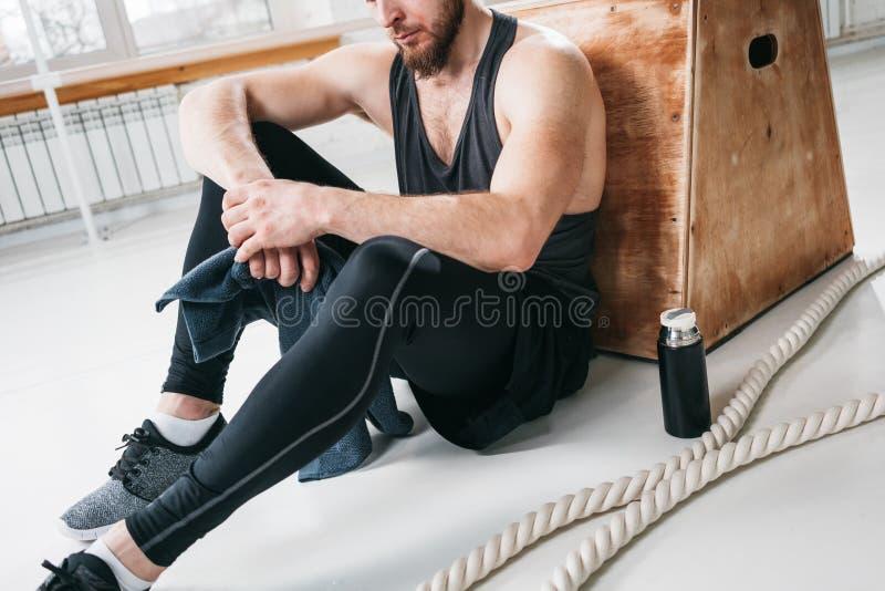Hombre apto sudoroso que se sienta en la toalla de la caja y del control a disposición después de entrenamiento cruzado intenso imagen de archivo
