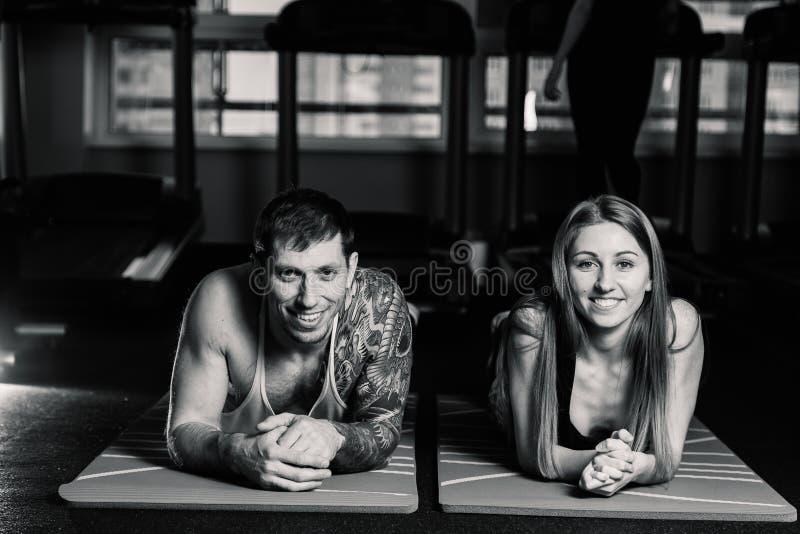Hombre apto y mujer juguetones que hacen aptitud del deportista del deporte del gimnasio del concepto de los músculos de la parte imágenes de archivo libres de regalías