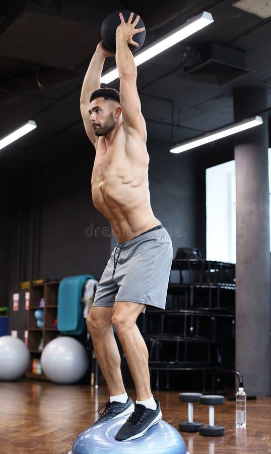 Hombre apto y muscular que ejercita con la bola de medicina en bola gimnástica del bosu del hemisferio en gimnasio fotografía de archivo