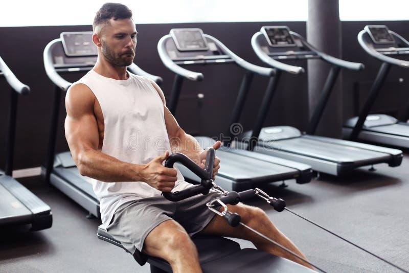 Hombre apto y muscular que realiza ejercicios en el simulador imágenes de archivo libres de regalías