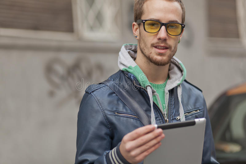 Hombre apuesto en la calle con el ordenador de la tablilla foto de archivo