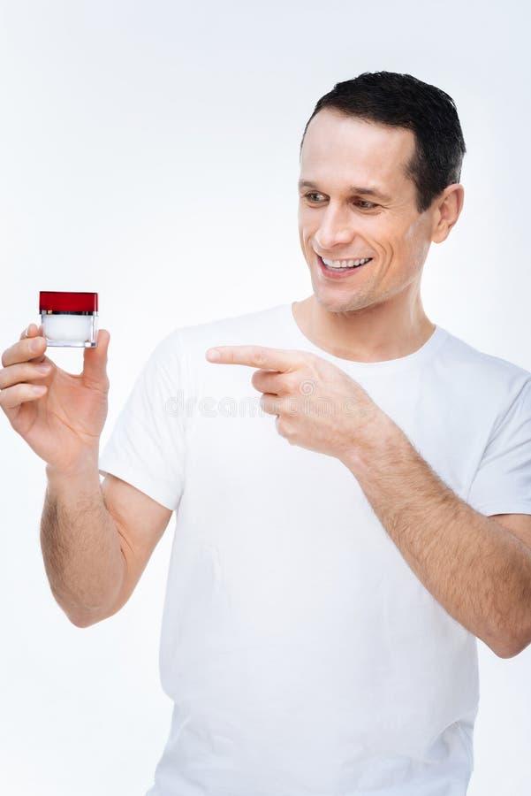 Hombre apuesto encantado que señala en la botella poner crema fotos de archivo