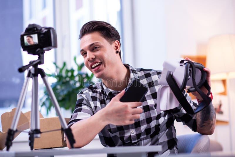 Hombre apuesto hablador en camisa a cuadros que explica características imagenes de archivo