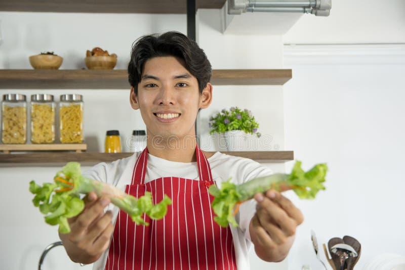 Hombre apuesto joven en el delantal rojo que presenta el menú sano del rollo de la ensalada con el smil, preparado en la cocina c imagenes de archivo