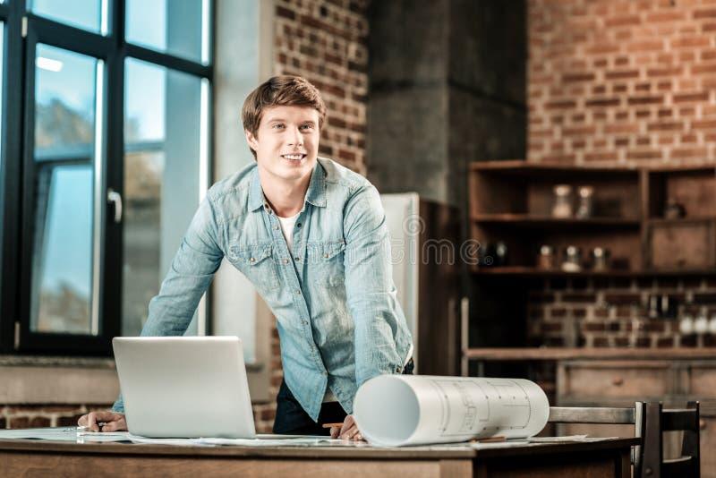 Hombre apuesto positivo que se inclina en la tabla fotografía de archivo libre de regalías