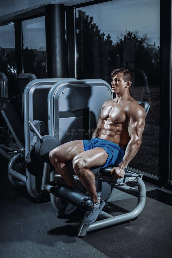 Hombre apuesto que hace extensiones de la pierna en una máquina en el gimnasio imagenes de archivo