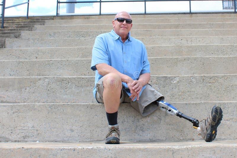 Hombre asentado con la pierna prostética extendida foto de archivo