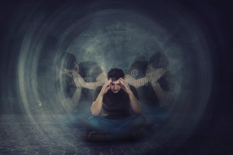 Hombre asentado en el piso, manos para dirigir, sufrir emociones partidas en diversas personalidades internas Salud mental multip imagen de archivo