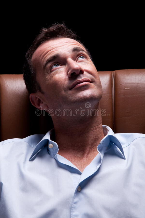 Hombre asentado en una silla, sonriendo y mirando para arriba a fotos de archivo