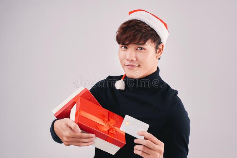 Hombre asiático atractivo joven en el sombrero de Santa Claus que sostiene la caja de regalo y la tarjeta de crédito imagenes de archivo