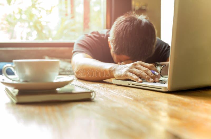 Hombre asiático cansado con la cabeza abajo en el ordenador portátil del ordenador mientras que trabaja imagen de archivo