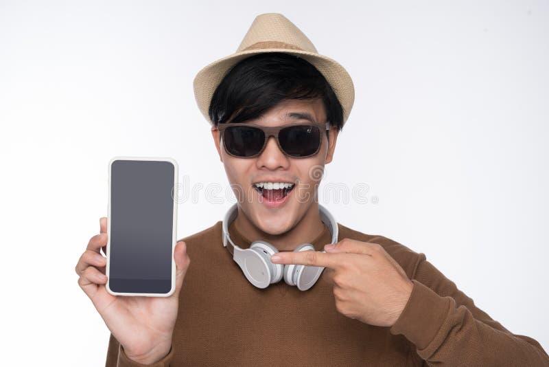 Hombre asiático casual elegante asentado en la silla, mostrando pedregal del smartphone fotografía de archivo libre de regalías