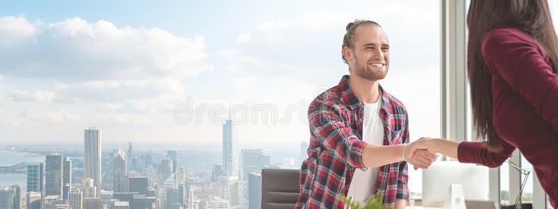 Hombre asiático caucásico joven confiado que sacude las manos con la mujer del socio en el acuerdo del negocio que sonríe junto s foto de archivo