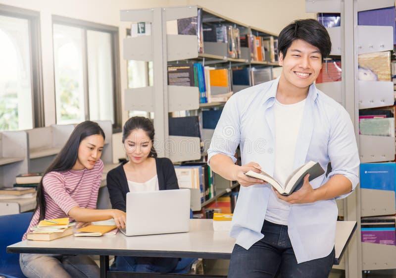 Hombre asiático con dos estudiantes universitarios asiáticos que usan el ordenador portátil en la biblioteca fotografía de archivo