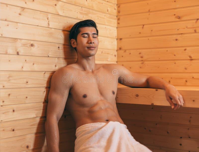 Hombre asiático con el cuerpo muscular que se relaja en sauna fotos de archivo libres de regalías