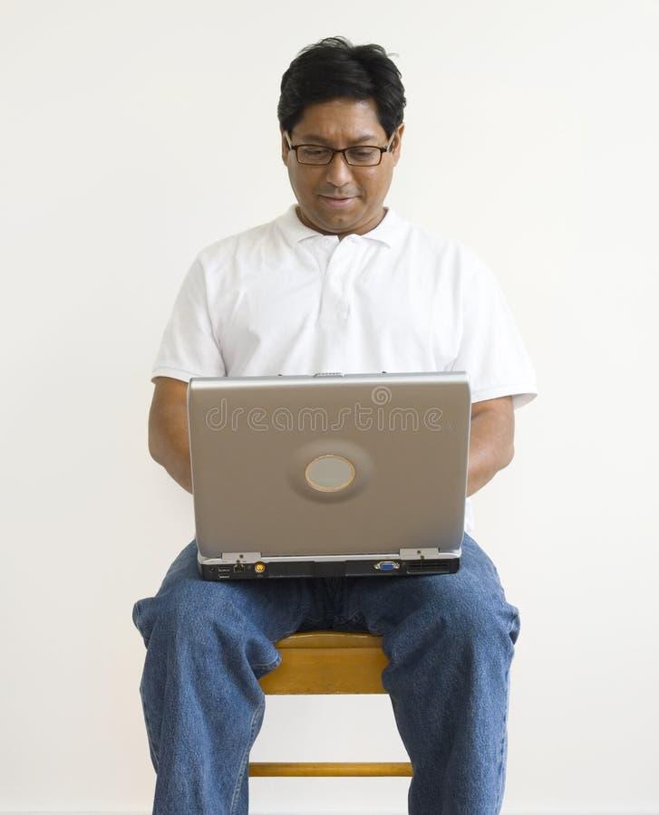Hombre asiático con una computadora portátil fotos de archivo