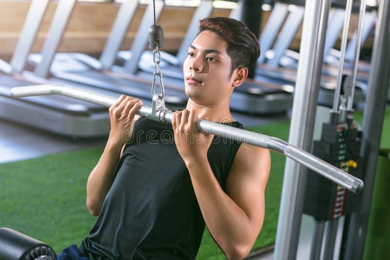 Hombre asiático del deporte que hace elevaciones Entrenamiento del Bodybuilder en gimnasia imagen de archivo libre de regalías