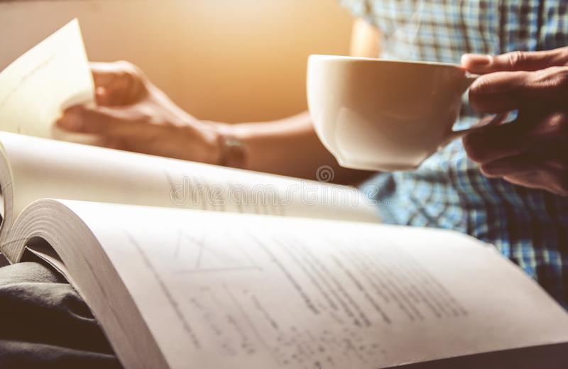 Hombre asiático del primer en la taza de la tenencia de la camisa del scottist de café que bebe y leer el libro fotografía de archivo libre de regalías