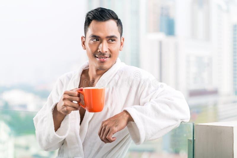 Hombre asiático en el frente de la mañana del horizonte de la ciudad imagen de archivo