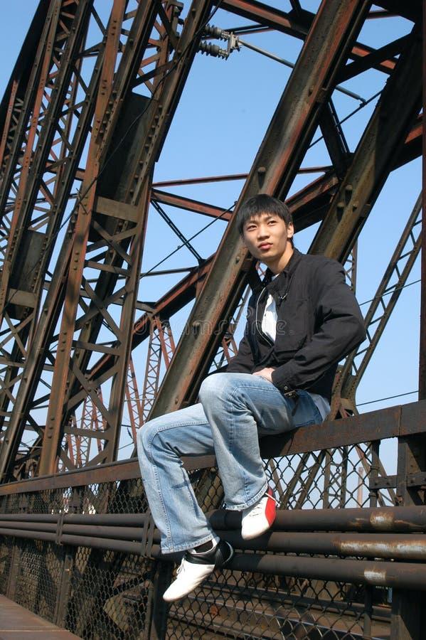 Hombre asiático en el puente fotografía de archivo