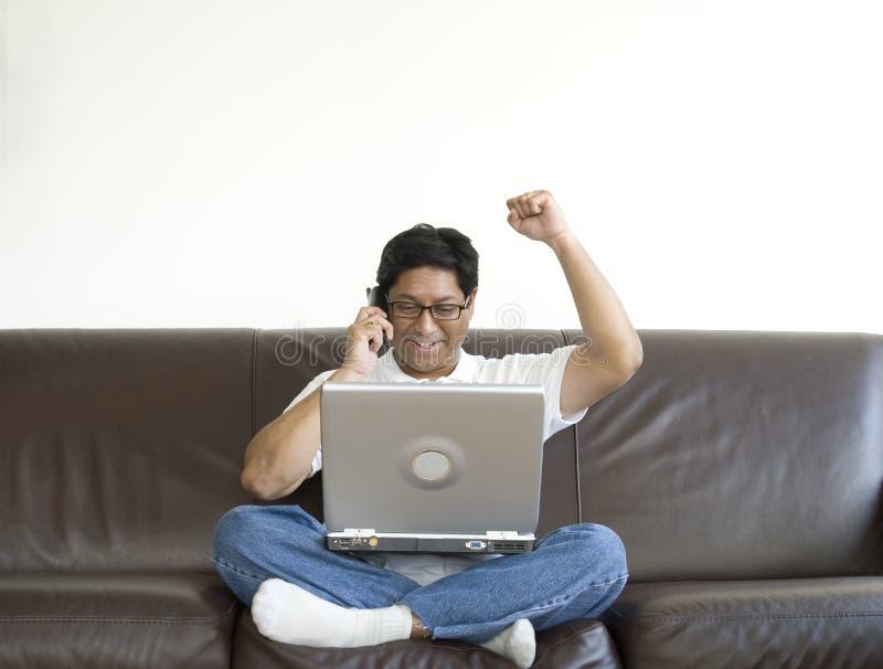 Hombre asiático feliz con la computadora portátil imagenes de archivo