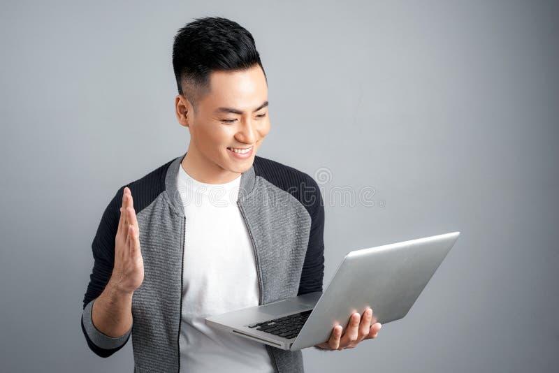 Hombre asiático feliz emocionado que mira la pantalla de ordenador portátil y el ce foto de archivo libre de regalías