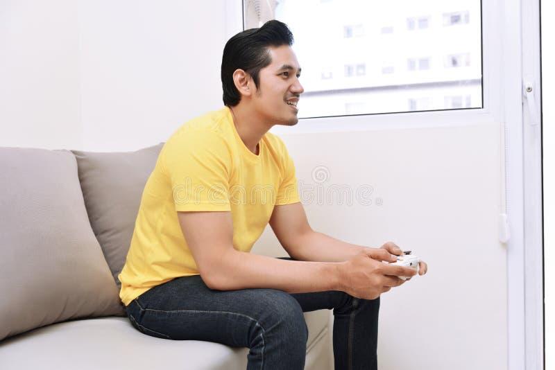 Hombre asiático feliz que lleva a cabo el gamepad y que juega a los videojuegos fotos de archivo