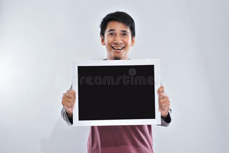 Hombre asiático hermoso joven feliz que lleva a cabo y que muestra la pizarra o al tablero en blanco listo para su texto foto de archivo