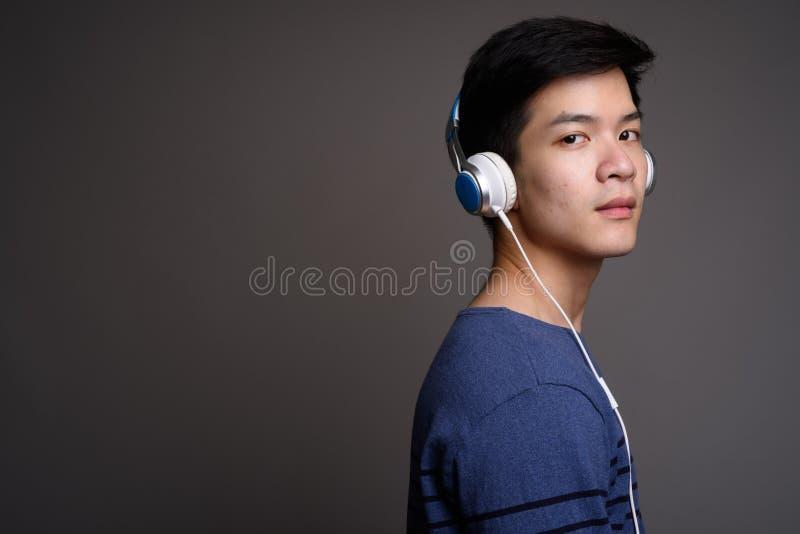 Hombre asiático hermoso joven que escucha la música con los auriculares fotos de archivo