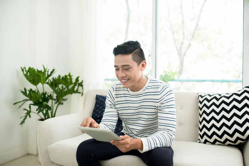 Hombre asiático hermoso joven que usa la tableta digital que se sienta en un sofá fotografía de archivo