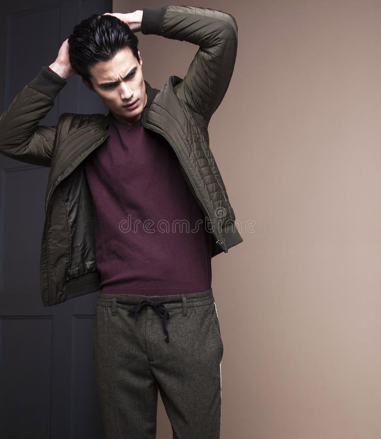 Hombre asiático hermoso joven real fresco en capa en el fondo negro p fotografía de archivo