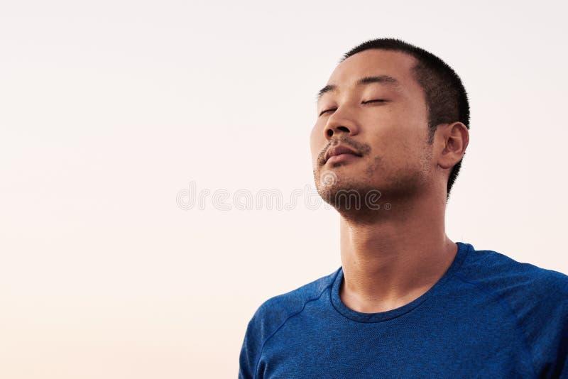 Hombre asiático hermoso que se relaja después de funcionamiento de la mañana imágenes de archivo libres de regalías