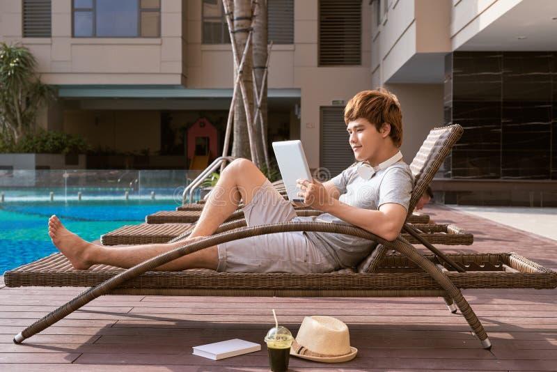 Hombre asiático hermoso que se relaja por la piscina y que lee el eBook fotografía de archivo libre de regalías