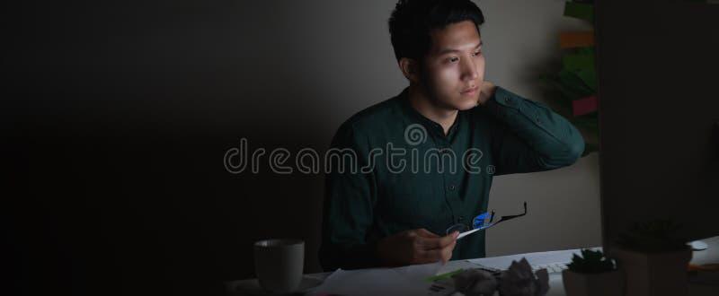 Hombre asiático joven atractivo que trabaja tarde en la noche que mira el ordenador portátil en la sensación oscura del escritori imágenes de archivo libres de regalías