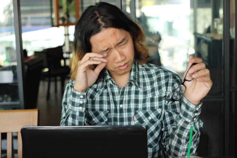 Hombre asiático joven con exceso de trabajo cansado con el ordenador portátil que es sobrecargado en oficina foto de archivo libre de regalías